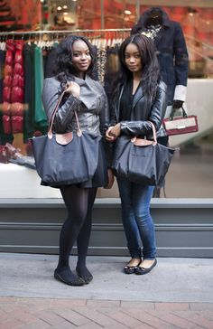 Street Style: Sherdelle and Tiyana play Longchamp snapsies in London! For more see bag snaps see http://www.handbag.com/handbags/street-style/