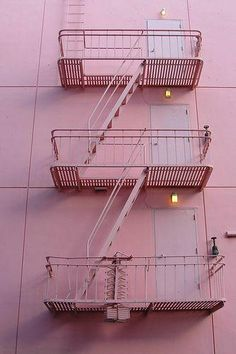 Pretty pink pastel building exterior with monochromatic fire escapes.