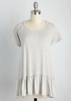 In this grey-and-white striped tunic, all your senses are invigorated! From the feel of its soft jersey knit to the sweet appearance of its solid hemline ruffle - and, don't forget the song its back-tied neckline inspires - this raglan top covers all the bases beautifully.