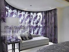 Silver chaise lounge in front of window with purple curtains
