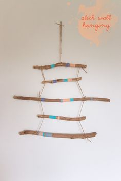 Painted stick wall hanging. I think this would be cute on a front door instead of a normal wreath.