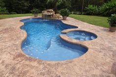 Saltwater fiberglass swimming pool by Dolphin Pools of West Monroe. Viking Pools Trilogy Pools. Spa with spillover with Rico Rock waterfall Pentair IC40 salt water system heater and Glacier pool cooler