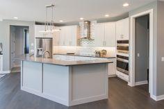 Kitchen: oak hardwood floors, painted cabinets, stainless steel appliances, quartz counter tops, glass tile backsplash