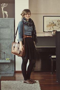 Flannel scarf, denim shirt, belted black skirt, brown leather shoes.