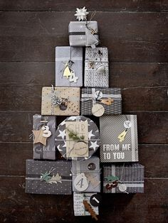 Grey, silver and white wrapped presents decorated with festive tape, star tags and metallic twine.