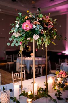 Wedding centerpiece at Piazza in the Village. Tall floral centerpiece of pink camellias, blush roses, and lush eucalyptus greenery. Mediterranean-inspired luxury wedding in Dallas/Fort Worth. Glamorous wedding reception. Texas weddings. DFW weddings.