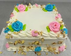 Buttercream cake topped with buttercream roses and sprinkled with sliced almonds