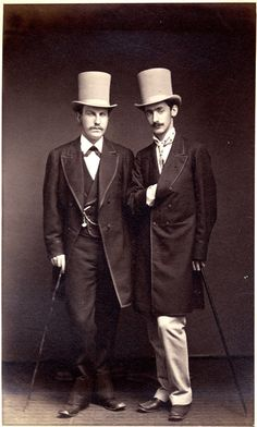 A pair of splendidly turned out and handsome young gents, in matching light top hats - perhaps cream or dove grey as they do not seem to be as pure white as the ribbon band around each! How I covet those long coats, each with a neat outline of binding adding a detail of distinction!