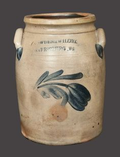 "Sold $ 150 One-Gallon Stoneware Jar with Cobalt Floral Decoration, Stamped ""COWDEN & WILCOX / HARRISBURG, PA,"" circa 1865, cylindrical jar with tooled shoulder, semi-squared rim, and applied lug handles, decorated with a brushed drooping tulip extending from a leafy stem. A chip to each handle. A few rim nicks. A 2"" hairline from rim."