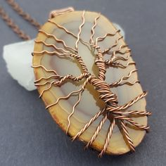 Handcrafted copper tree of life necklace featuring a natrual, soft brown agate stone. This natural stone is semi-transparent, when held to the light, it glows with beautiful details.   ☆ Agate represents grounding, self-esteem, and balance.  ★ Pendant Size: approximately 2.2 inches (55mm) tall, 1.3 inches (33mm) wide   Available in my #Etsy store:  http://etsy.me/2De1kZx