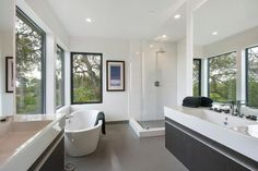 Natural light and white walls create a bright and refreshing look in this modern bathroom. A glass shower and luxurious soaking tub allow you to enjoy the outdoor view while you clean up and relax. A large vanity mirror reflects the light and scenery. Dark cabinetry is topped with a thick white countertop to finish the design.