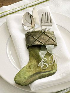 A stocking favor serves as both a place setting and a flatware corral. Stitched from two pieces of green iridescent fabric, the favor is personalized by attaching a pair of metal letters with a piece of sheer ribbon.