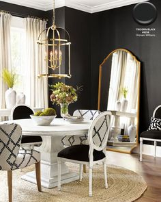 Dining room with walls in Sherwin Williams' Tricorn Black, a jute rug, and white chairs and table