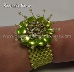 This simple yet stunning Wrist Corsage is handcrafted with Gold Diamante Brooch , Ivory Pearl Sprigs , Lime Green Buttons and created on a Lime Green Bracelet