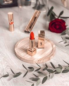 "A flatlay of yves-saint-laurent lipstick ""rouge couture"". A nice orange-red gloss."