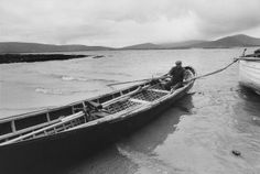A man sits in a currach boat, Aran Islands, Ireland, 1974.