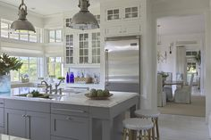 Gray kitchen cabinets, white marble counters, open, bright, two separate sinks, lots of windows, light colored floor, very neutral.