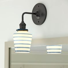 Schoolhouse-style sconces with blue-striped shades add some whimsy to the bathroom; their aged-bronze finish keeps them grown up. From @schoolhouseelec