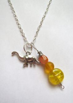 Dinosaur pendant necklace with Czech glass and Carnelian.  $22, free US shipping.  http://www.emeraldcitycustomjewelry.com/