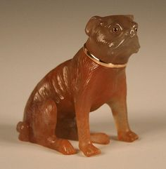 A Russian carved hardstone figure of a seated pug, early 20th Century, probably by Fabergé, wearing a gold collar and inset with gold mounted ruby eyes, height approx 5.2cm (repaired leg, minor chips and possibly replaced collar)
