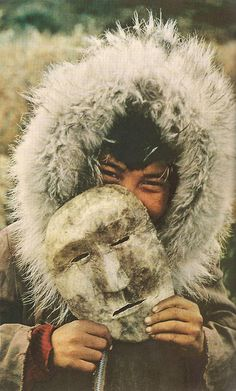 July, 1959 Inuit boy at Anaktuvuk Pass, which belongs to the last of Alaska& nomads - descendants of prehistoric immigrants from Asia. He plays with a caribou-hide face, a toy counterpart of tribal spirit masks. Wolverine fur fringes the parka. Arte Inuit, Inuit Art, We Are The World, People Around The World, Around The Worlds, Inuit People, Hidden Face, People Photography, Color Photography