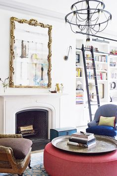 Tall bookshelf with ladder in bright living room with fireplace