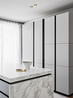 black and white sleek modern kitchen, black faucet, marble counter, white cabinets