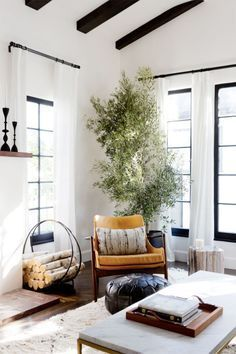 tree in living room, black window frames, log holder, mid-century arm chair, coffee table, moroccan pouf