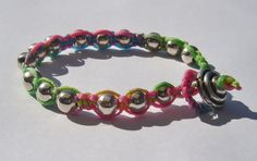 Wrap Bracelet with Silver coloured balls on Multi-coloured Waxed Linen. €15,00, via Etsy.