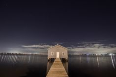Panoramic view from the jetty of a lakehouse with the cityscape in the background at night.