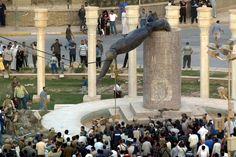 Iraqis watch a statue of Saddam Hussein fall in Baghdad