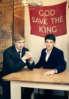 """Bradley James, Colin Morgan Radio Times 2012<----- I know this is 100% not okay, but the sign behind him says""""God save the king"""" and that hurt me."""
