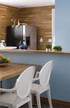 Cadeiras Louis Ghost brancas, da Kartell. No piso, cerâmica 7 x 7 cm pintada a mão (Brennand). Tinta acrílica azul (Suvinil, ref. C 072*) na parede.