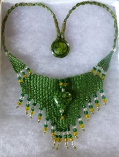 """Green Flower Heart"" - 2013, Fixed Length Choker, Vintage Button, Glass Bead Centerpiece, AVAILABLE. Woven by Terri Scache Harris, theravenscache.shutterfly.com   Hand woven, handwoven, weaving, weave, needleweaving, pin weaving, woven necklace, fashion necklace, wearable art, fiber art."