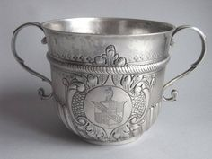 QUEEN ANNE. A Britannia Standard Porringer. The Porringer is of large size and is decorated on the lower half of the main body with alternate lobes and flutes. The upper section displays a protruding lobed band and various bands of punched foliate motifs. The front of the main body is engraved with a Armorial on an oval disc surrounded by a cartouche of scrolls, scale work and acanthus foliage.