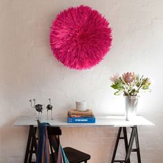 This neon pink Juju hat punches up the blank wall in this office space. via Safari Fusion - Designer Obsessions: Juju hats