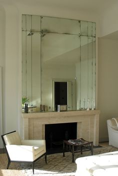 Deco travertine mantle, t.h. robsjohn-gibbings chair & thebes stool, plus the foxed, over-mantle mirror, create a good vignette.