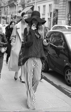 Striped pants, over-sized knit sweater and black floppy hat