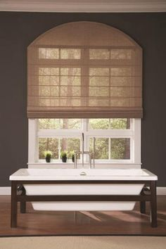 Woven wood roman shade with specialty shape arch window covering.