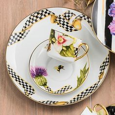 Thistle & Bee Dinner Plate - Ribbon: There's been quite a buzz about our take on formal china. Handcrafted in Portugal, the Thistle & Bee Dinner Plate—Ribbon is framed with a Courtly Check ribbon decal and trimmed in gold lustre. A treat on its own, but even sweeter when paired with the complementary Garland Dinner Plate and the rest of the Thistle & Bee Collection.