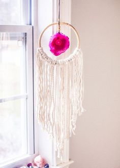 Shackin up with a pop of color! This beautiful wall hanging is made with a rattan hoop featuring a bright agate at the center and soft cotton fringe on the bottom. A perfect window adornment or dreamy