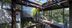 Passarela com piso de vidro, casa com grandes janelas, aço e vidro, corrimão cromado. Teto de vidro e vigas metálicas. Casa no bosque na Cidade do México por Grupoarquitectura