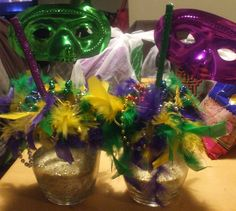 Marti gras themed center pieces, clear vases, salt mixed with glitter, masks from $1 store, feather boa, and wooden painted sticks...made great center pieces for mother in law 50th bday party