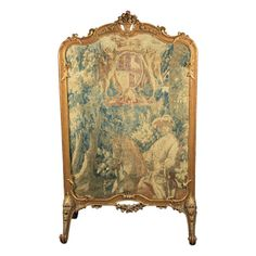"""An antique carved and gilt Rococo style fire screen with an 18th century French tapestry of a horseman in a forest surmounted by a coat of arms.  Frame is late 19th century. CIRCA: 18th Century DIMENSIONS: 55.75"""" h x 34"""" w x 18.5"""" d PRICE: $3,895"""
