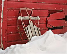 """Sled on Red"" by Nikolyn McDonald is a vintage Flexible Flyer steel runner sled standing against the side of an old red barn after its use on a winter day. farm,snow,fun,rusty,toy,child,play,outdoor,past,days,bygone,era,wholesome,activity,christmas,december,january,february,holiday,season,wooden,building,drift,nostalgia,memory,memories,remember,old-fashioned,nikki,nikolyn,mcdonald"