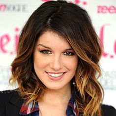 roots are dark with a highlighted caramel framing her face. great look for dark hair brunettes