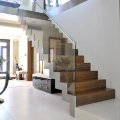 a modern zigzag staircase with frameless glass balustrade