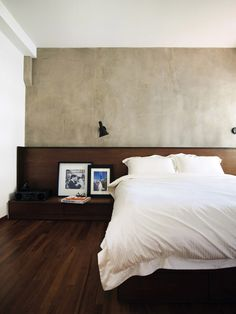 The organic textures of concrete and wood create a sense of calm and cosiness in the master bedroom