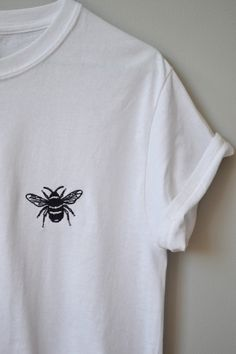 The cutest Bee embroidered in black onto a unisex white t-shirt for a loose fit. Model wears a size small ,sleeves have been rolled to style. Also available as a black tee with silver stitching either can be cropped or full length (hem will be left raw if cropped). Sizing as follows -S 34/36 M 38/40 L 42/44 . Please allow 2-3 working days for me to embroider and ship your order, you will be notified when your garment is being embroidered and given a shipping date :)