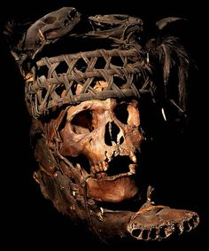 IFUGAO TRIBE: HUMAN HEADHUNTED  TROPHY SKULL MOUNTED ON A BOVINE'S JAW  WITH A RATTAN HAT MADE FROM TWO ANIMAL SKULLS  HUMAN BONE, ANIMAL JAW, RATTAN, FEATHERS  THE IFUGAO TRIBE, FROM THE PHILIPPINES,  AFTER HEADHUNTING MOUNT HUMAN  SKULLS ON SACRIFICED BOVINE AND BOAR SKULLS.